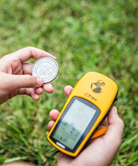 Image of a child holding a coin with a 4-H logo and a Garmin GPS navigator